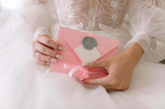 Die braut hält eine einladung zur hochzeit in einem rosa umschlag.
