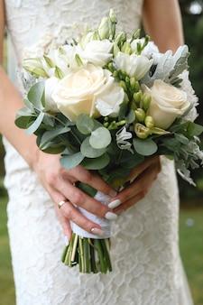 Die braut hält einen schönen weißen hochzeitsblumenstrauß. nahansicht.