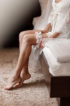 Die braut hält in der hand aufgeben strumpfband im hotelzimmer. morgen vorbereitung hochzeitskonzept.