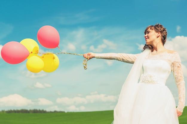 Die braut hält luftballons in den händen
