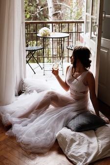 Die braut im penioire sitzt mit einem glas champagner auf dem balkon