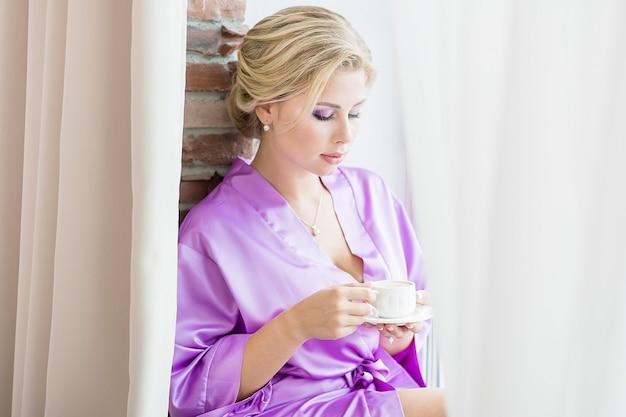 Die braut in einem lila seidengewand bereitet sich morgens auf die hochzeit vor