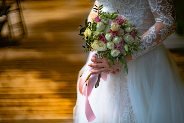 Die braut in einem luxuriösen weißen spitzenkleid hält einen strauß rosen in den händen im zimmer. nahansicht