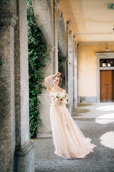 Die braut in einem schönen kleid mit einem strauß rosa blumen steht mit ihrer hand im gewölbesaal