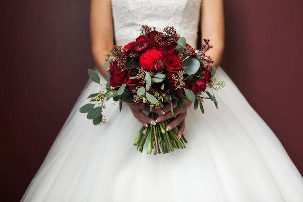 Die braut in einem weißen eleganten hochzeitskleid, das einen hochzeitsblumenstrauß hält.