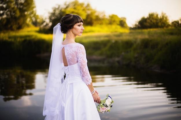 Die braut in einem weißen kleid auf naturhintergrund. hochzeitsfotografie.
