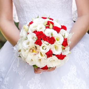 Die braut in einem weißen kleid bei einer hochzeitszeremonie mit einem rosenstrauß.