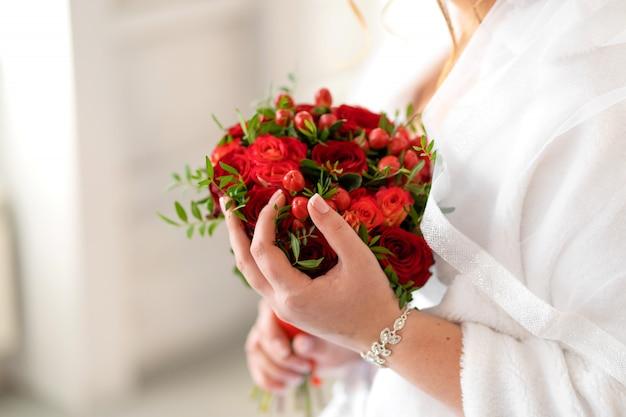 Die braut in einem weißen kleid hält in ihren händen einen stilvollen hochzeitsstrauß aus roten rosen. hochzeitsdetails.
