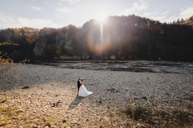 Die braut in einem weißen kleid und bräutigam steht in der nähe des flusses und umarmt und sonnenschein