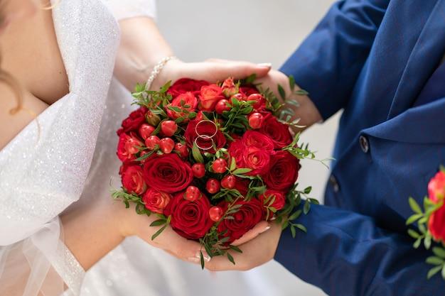 Die braut in einem weißen kleid und der bräutigam halten einen stilvollen hochzeitsstrauß aus roten rosen. hochzeitsdetails.