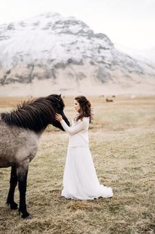 Die braut in einem weißen kleid und einem blumenstrauß in den händen streichelt ein pferd mit schwarzer mähne im gesicht