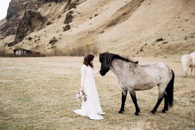 Die braut in einem weißen kleid und einem blumenstrauß in den händen streichelte ein pferd mit einer schwarzen mähne im gesicht