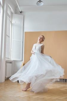 Die braut ist eine frau in einem leichten sommerhochzeitskleid, die am fenster steht. blondes mädchen mit perfektem haar und schönem make-up