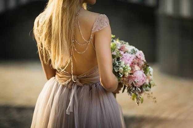 Die braut ist zurück in einem spitzenhochzeitskleid. frau hält einen blumenstrauß von pastellblumen und grün