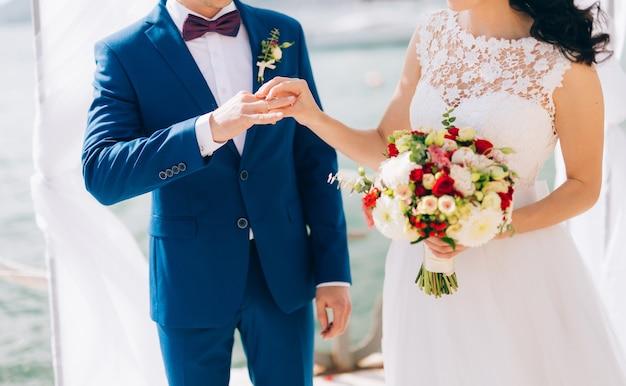 Die braut legt dem bräutigam bei der trauung den ring an