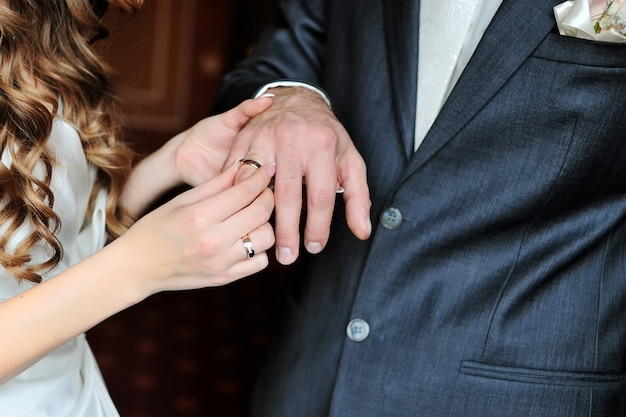 Die braut legt den ehering an den finger des bräutigams