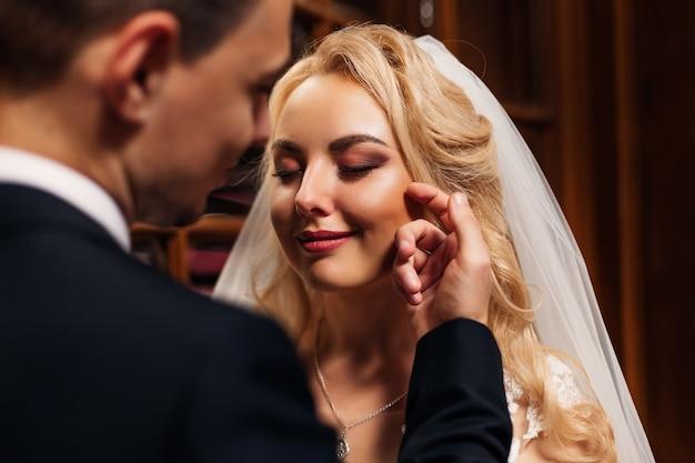Die braut mit dem schönen make-up schloss die augen und der bräutigam berührt ihr gesicht mit seiner hand