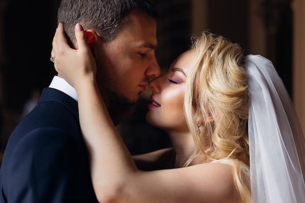 Die braut mit dem schönen make-up schloss die augen und umarmte den bräutigam