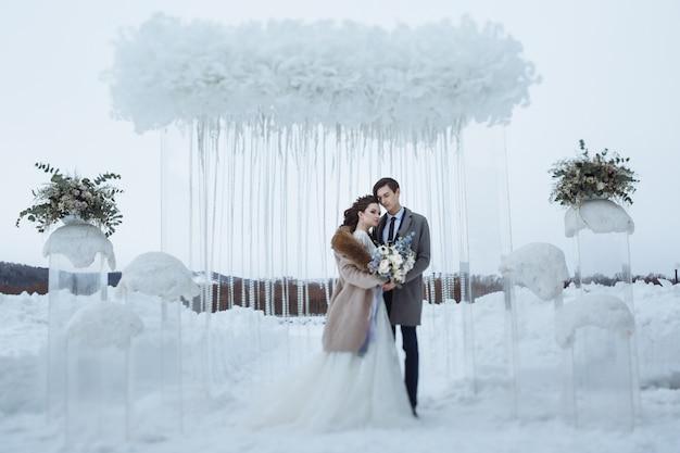 Die braut mit einem schönen blumenstrauß und der bräutigam beim hochzeitswinterschießen. junge leute stehen vor dem hintergrund der winterhochzeitsdekorationen
