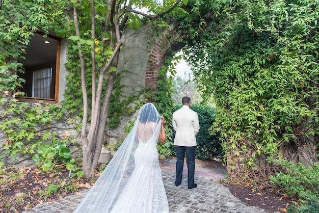 Die braut nähert sich dem bräutigam, der vor einem natürlichen bogen steht