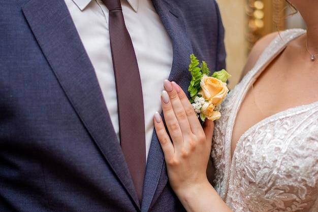 Die braut passt das knopfloch an ihren bräutigam an