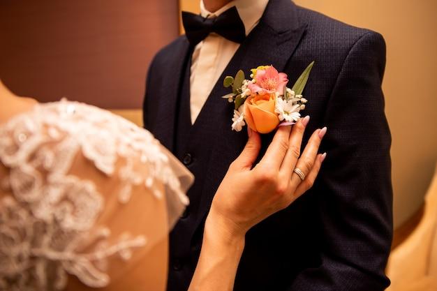 Die braut passt den boutonniere an den bräutigam an