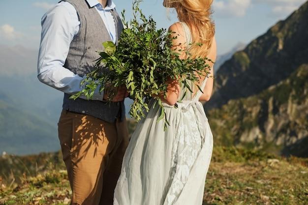 Die braut schloss die augen und flüstert ihrem verlobten etwas zu, hintergrund von bergen