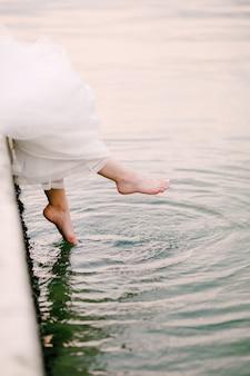 Die braut sitzt auf dem pier und lässt ihre nackten füße im wasser baumeln, aus dem die beine hervorschauen