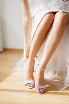 Die braut sitzt auf einem stuhl in einem hotelzimmer und zieht während der hochzeitsvorbereitungen sandalen an, nahaufnahme