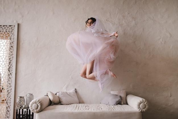 Die braut springt auf die couch. die braut versammelt sich am morgen. stilvolles rosa hochzeitskleid.