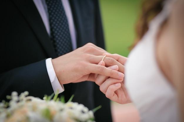 Die braut steckt den ring an den finger des bräutigams