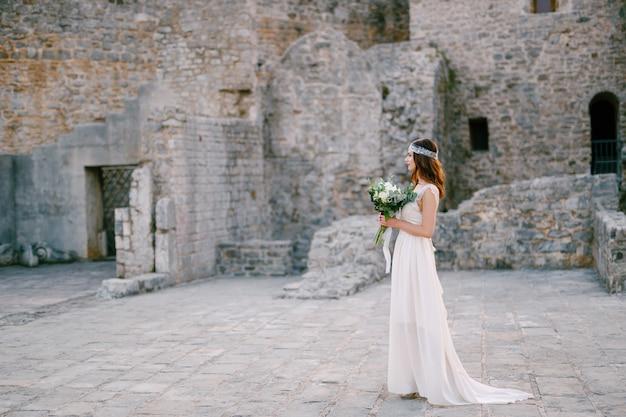 Die braut steht auf dem platz in der nähe der burgmauer in der altstadt von budva und hält einen blumenstrauß in den händen. hochwertiges foto
