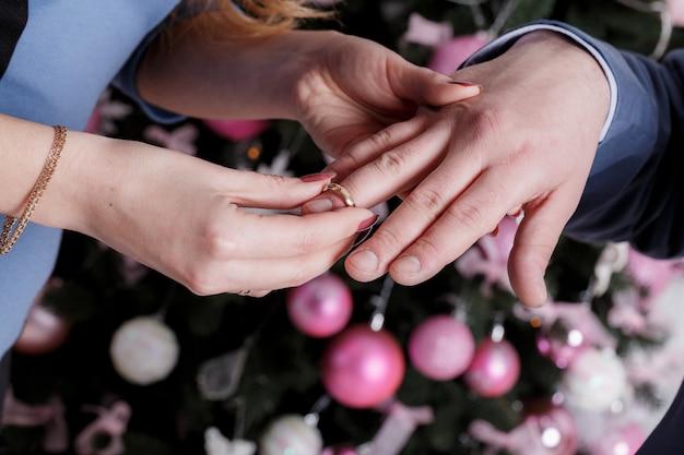 Die braut trägt den ring am finger des bräutigams am hochzeitstag. liebe, glücklich heiraten konzept.