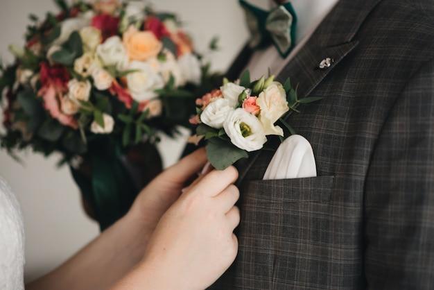Die braut trägt einen boutonniere für den bräutigam. stilvolles hochzeitsmorgenfoto