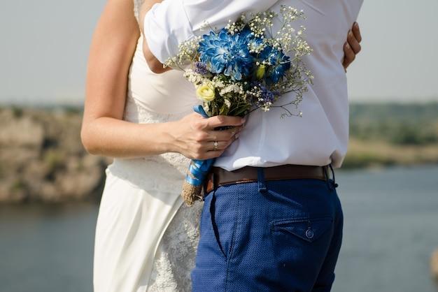 Die braut umarmt den bräutigam und hält einen brautstrauß mit blauen blumen auf dem hintergrund des flusses