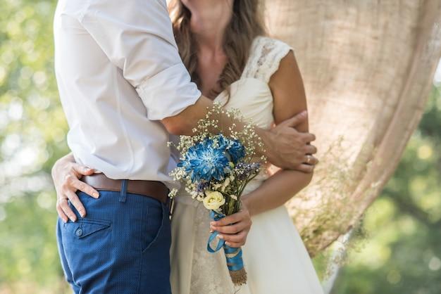 Die braut umarmt den bräutigam und hält einen brautstrauß mit blauen blumen auf dem hintergrund des waldes