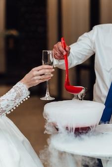 Die braut umarmt den bräutigam und hält einen brautstrauß mit blauen blumen auf waldhintergrund