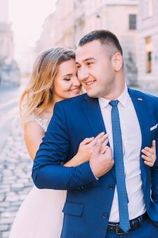 Die braut umarmt den bräutigam von hinten und sie schließen die augen