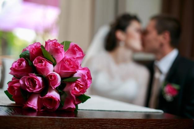 Die braut umarmt und küsst den bräutigam sanft aus der nähe. hochzeitstag. hochzeitspaar verliebt in innen an der wand. brautstrauß aus leuchtend rosa rosen und jungvermählten. liebesgeschichtenkonzept