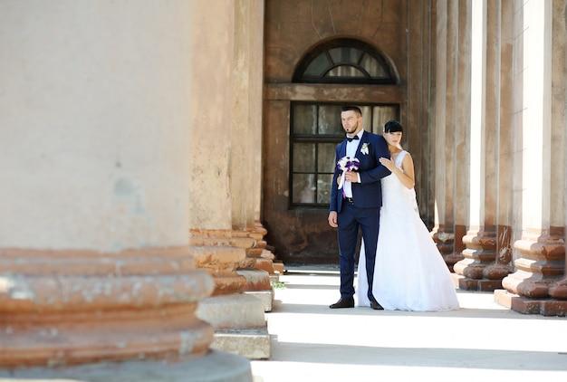 Die braut und der bräutigam auf dem hintergrund eines altbaus mit spalten