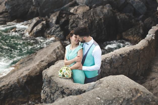 Die braut und der bräutigam auf natur in den bergen nahe dem wasser. anzug- und kleiderfarbe tiffany. küssen und umarmen.