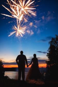 Die braut und der bräutigam beobachten das feuerwerk, silhouette