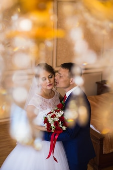 Die braut und der bräutigam, die im hotelzimmer, einen hochzeitsblumenstrauß halten küssen