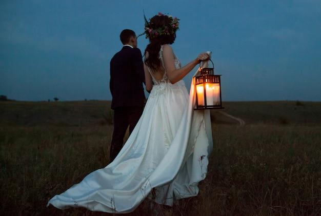 Die braut und der bräutigam gehen bei sonnenuntergang.