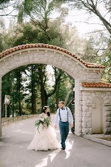 Die braut und der bräutigam gehen händchen haltend entlang der straße im park neben einem schönen backsteinbogen