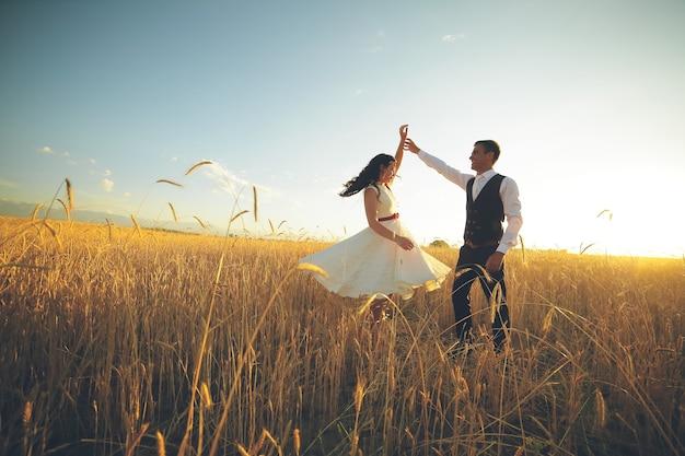 Die braut und der bräutigam halten hände, die im park tanzen.