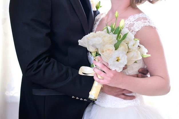 Die braut und der bräutigam mit dem hochzeitsstrauß der weißen rosen schließen zusammen