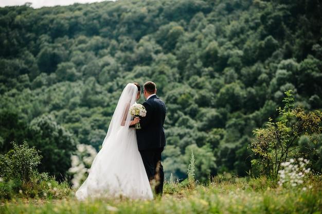Die braut und der bräutigam mit einem hochzeitsblumenstrauß, halten sich an den händen und stehen zurück mit blick auf die berge.