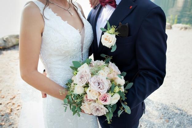 Die braut und der bräutigam mit einem hochzeitsstrauß in ihren händen. bräutigam und braut, die hände auf dem blumenstrauß halten.