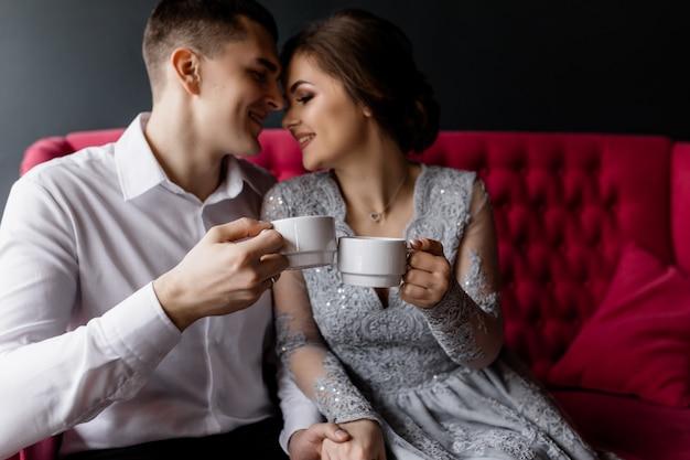 Die braut und der bräutigam mit kaffeetassen umarmen sich